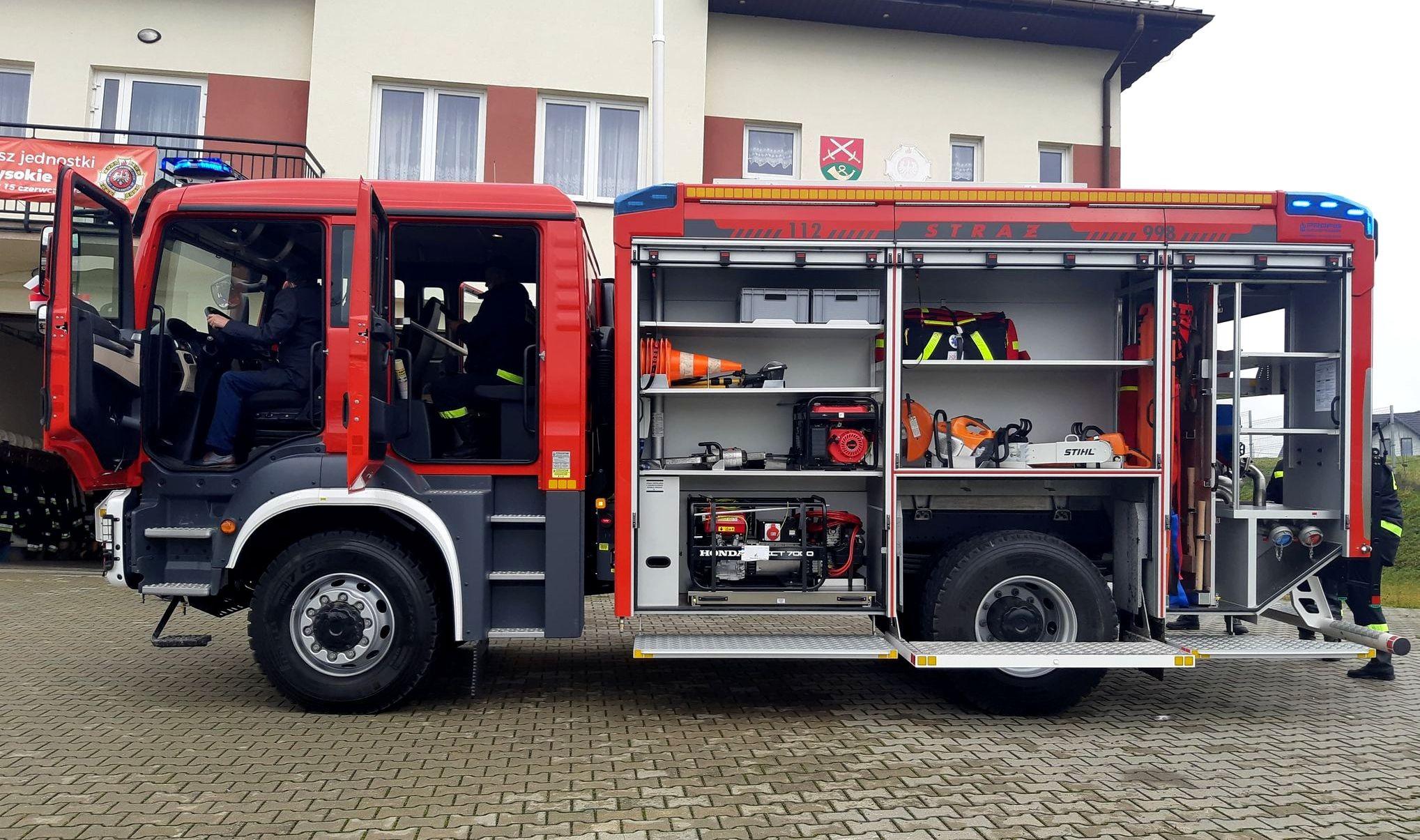 Wóz strażacki z otwartymi komorami na sprzęt pożarniczy na tle budynku OSP.